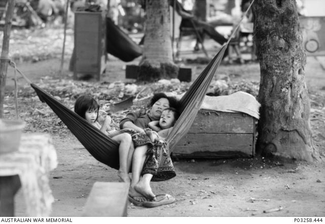 Kamodža 1993 - Na ulici v Phnom Penhu odpočívá matka v houpací síti se svým synem a dcerou, zatímco čekají na zákazníky u jejich stánku s ledem. Australian War Memorial Archive
